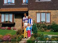 Father, mother and two children standing outside a house