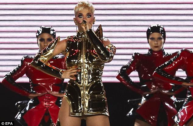 Sexy on stage: The shoe designer graced the stage in a gold outfit in thigh-high closed-toe, high-heeled boots
