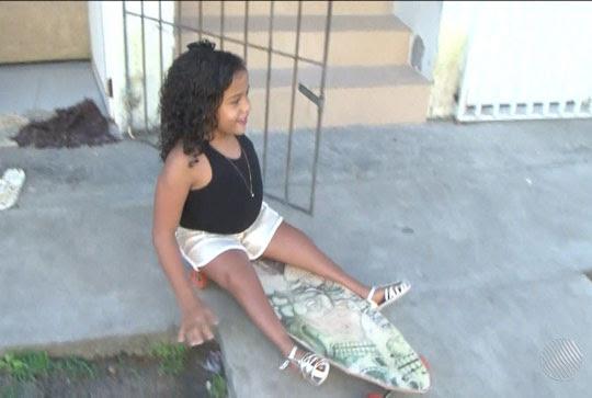 Com atrofia nas pernas e sem dinheiro para cadeira de rodas, menina de 8 anos usa skate para se locomover na Bahia