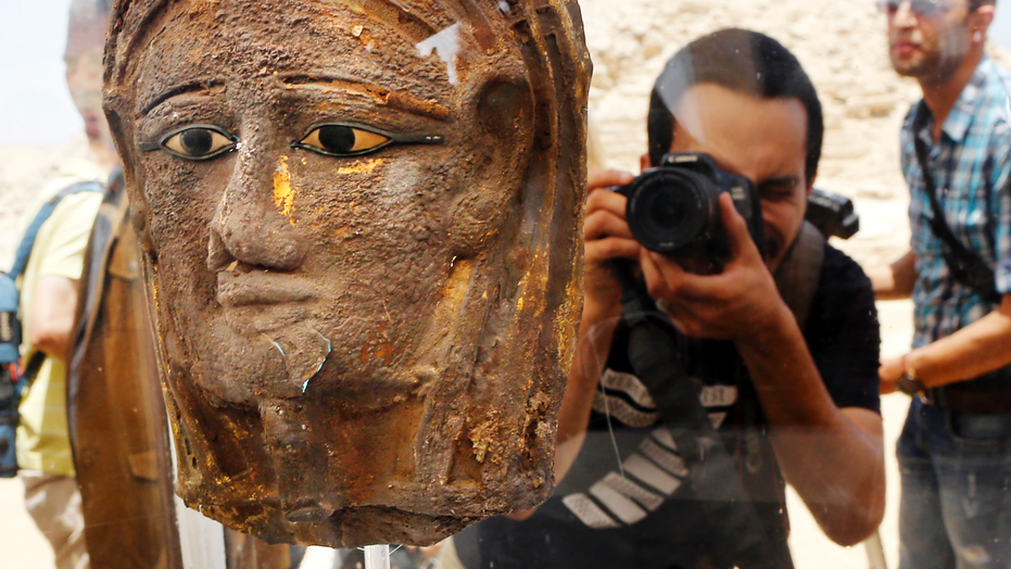 A photographer films a gilded silver mummy mask found on the face of the mummy of the second priest of Mut, as it is displayed during a press conference in front of the step pyramid of Saqqara, in Giza, Saturday, July 14, 2018.
