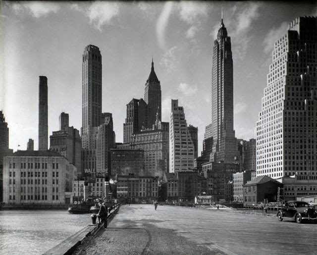 Manhattan Skyline: I. South Street and Jones Lane, Manhattan. Looking from pier toward Manhattan, tugboats moored left, Downtown Skyport, right, skyscrapers in the background.