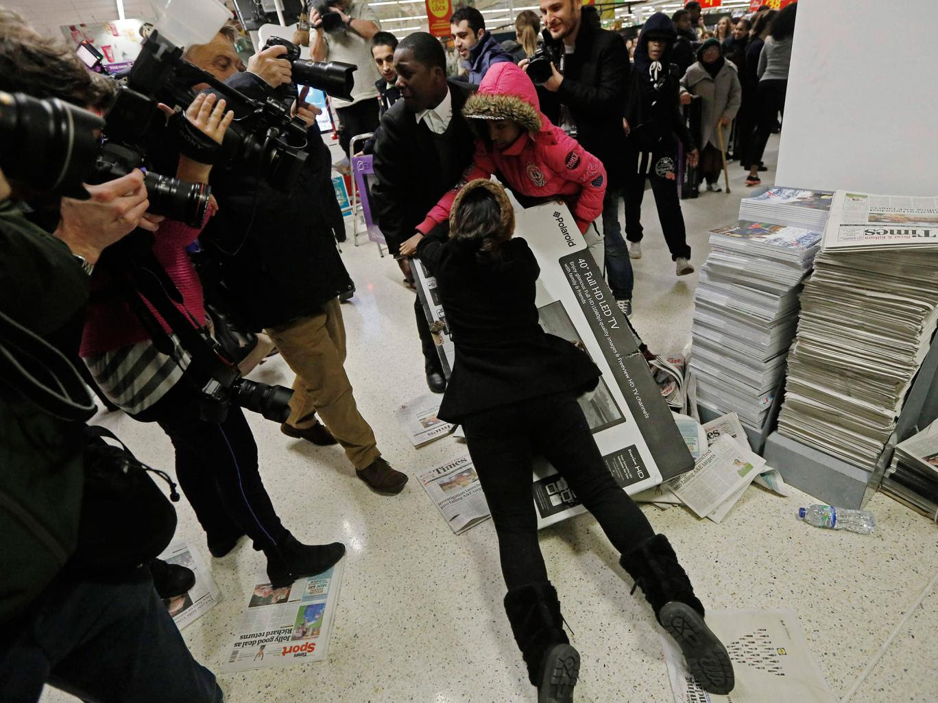 Shoppers wrestle over a television at an Asda superstore in Wembley REUTERS - Luke MacGregor