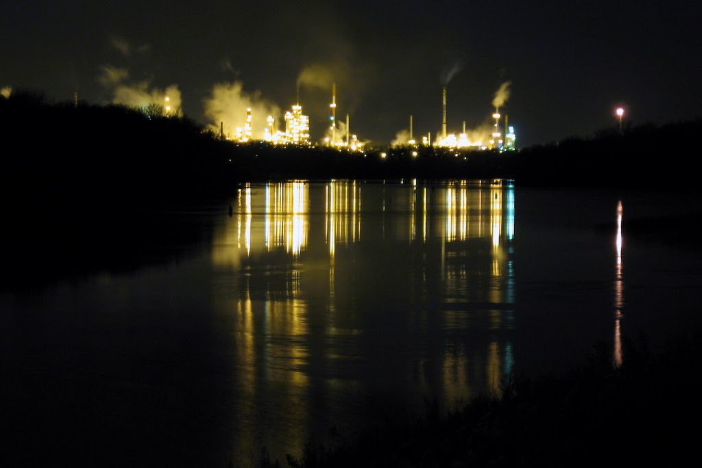 Night time photograph of the Ashland Oil plant in Newport with streaks of lights on the Mississippi River waters