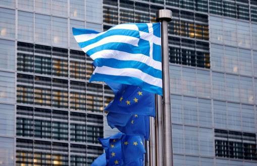 A Greek national flag flies next to European Union flags outside the EU Commission headquarters in Brussels November 13, 2012. REUTERS/Francois Lenoir (BELGIUM  - Tags: POLITICS BUSINESS)