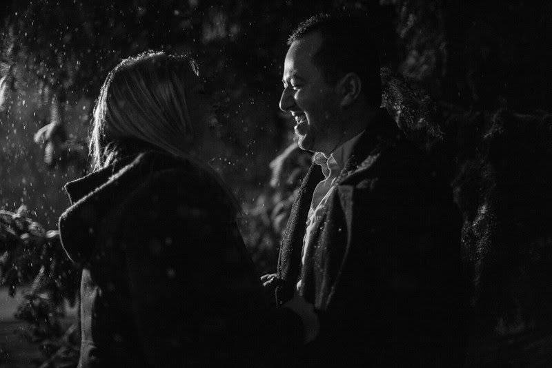 Outdoor engagement photos in an urban winter wonderland in downtown Rockford IL with falling snow at night.