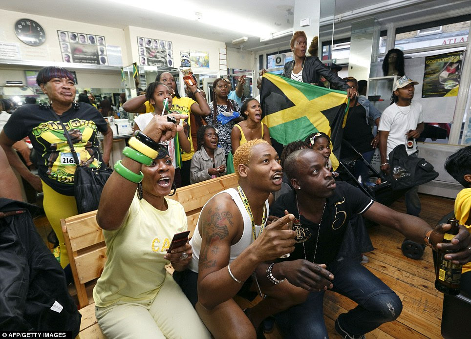 Fervour: Spectators from the Jamaican community in Brixton, south London, watch their heroes in action on television on the 50th anniversary of the Caribbean island's independence from Britain