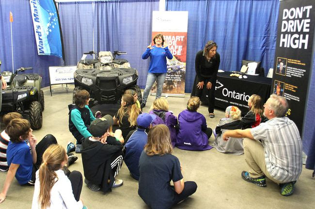Schoolchildren and their teacher listen as Denise Erickson, left, and Melanie Trottier talk about ATV safety during the Racing Against Drugs event in Kingston on Tuesday. Grade 6 children rotated through interactive displays on healthy, substance-free living. (Michael Lea/The Whig-Standard)