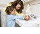 a mother teaching her child how to wash his hands