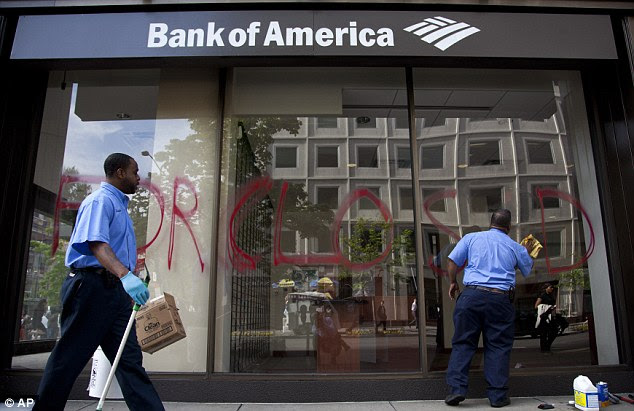 Vandalised: Workers clean windows of a Bank of America branch in Washington. Activists were also accused of vandalism in San Fransisco after they held a march on Monday night ahead of the day of action