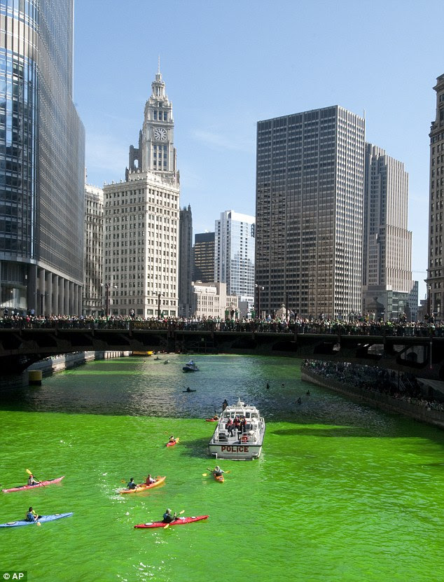 Eye catching: The river's dye drew thousands along its bank this morning, with a few kayakers paddling in the water, to get a glimpse of the bright green water
