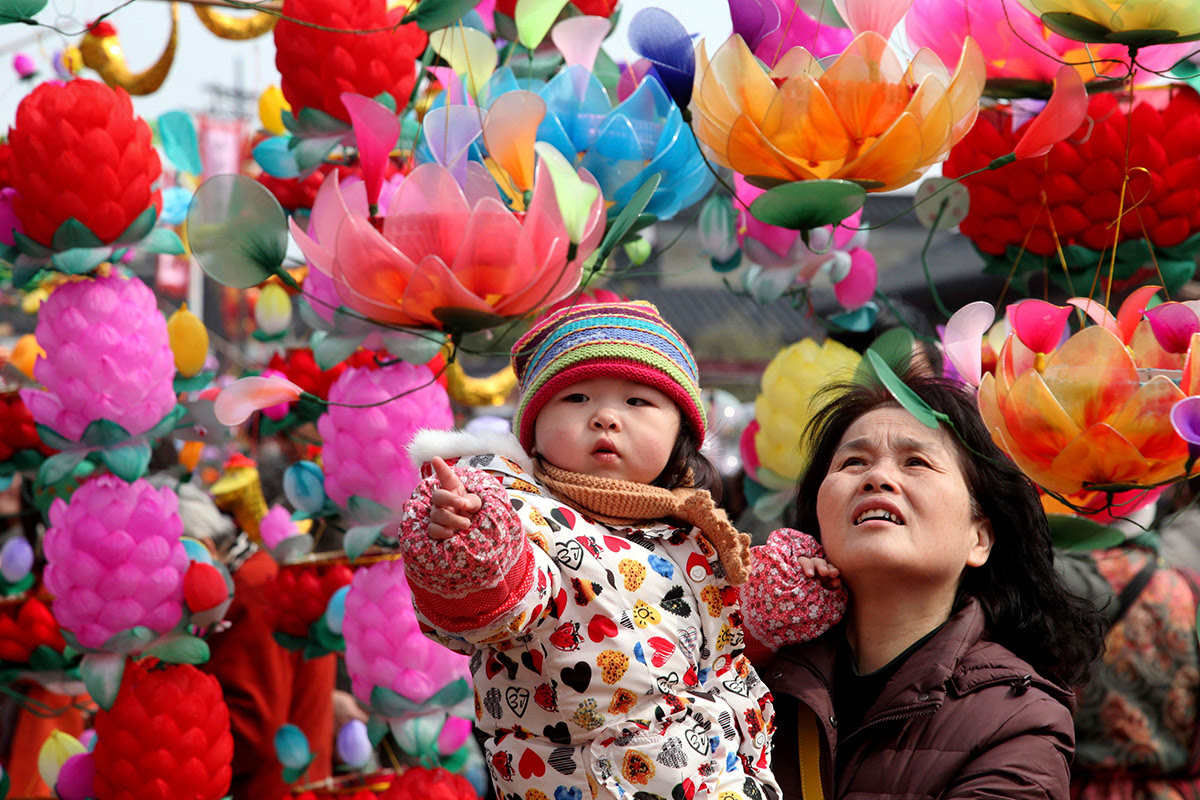 A girl being carried by her grandmother points to a lantern at a market in Nanjin. New Year's markets sell all the items families need to decorate their homes at this time of year, such as fireworks and lanterns