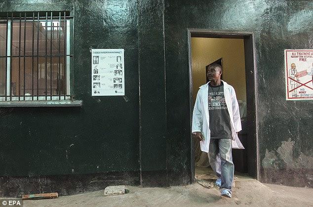 Resposta Médico: Uma enfermeira liberiano passa por um cartaz ilustrando passos para enfermeiros para colocar em roupas de proteção exibido na Redenção Hospital onde uma enfermeira teria morrido do vírus Ebola em Monrovia