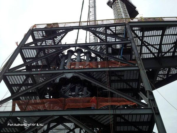 The first segment of the antenna spire is lowered through the middle of the scaffolding atop 1 WTC, on January 15, 2013.