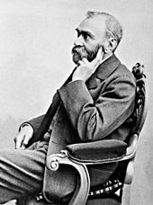 A black and white photo of a bearded man in his fifties sitting in a chair.