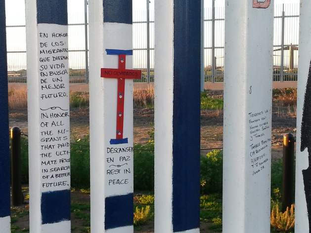 Memorial to migrants who died crossing, on U.S.-Mexico border fence, Tijuana. Credit: Peter Costantini