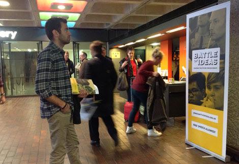 Un asistente observa un cartel en la 'Batalla de las Ideas'. | C.F.