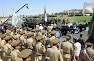 In this photo released by the Syrian official news agency SANA, Syrian Army trucks pass in front of honor guards as they carry the coffins of the three members of Syrian President Bashar Assad's inner circle, who were killed on Wednesday by a bomb, during their their funeral processions, in Damascus, Syria, Friday, July 20, 2012. A bombing in Damascus claimed by Syrian rebels Wednesday killed key figures in President Bashar Assad's inner circle. (AP Photo/SANA)