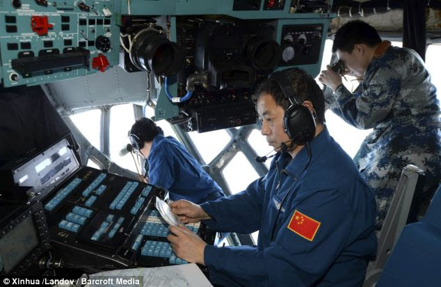 Crew members of the Chinese Air Force search the sea areas where the missing Malaysia Airlines flight MH370 lost contact