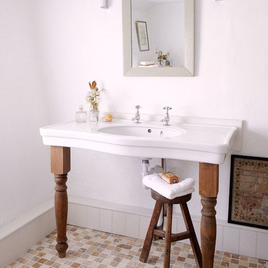 Open vanity with salvaged top and wooden furniture legs in a Dorset cottage bathroom