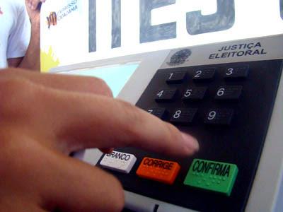 Dedo prestes a apertar a tecla confirma em urna eletrônica de votação