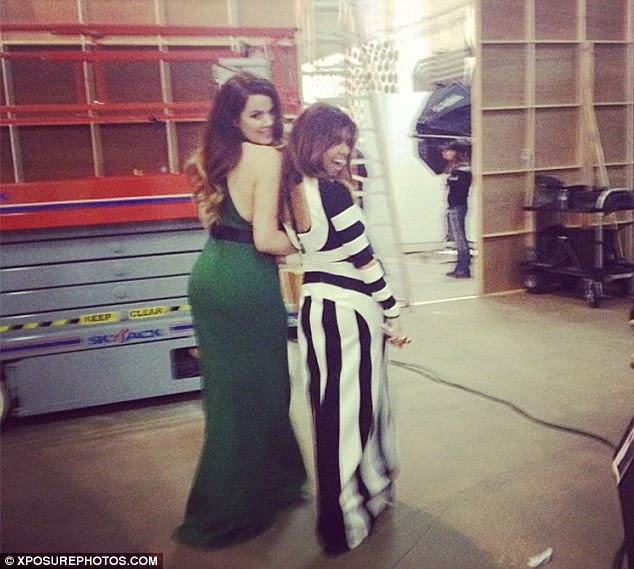 More glam: Khloe wore a vibrant green frock next to a stripey Kourtney for the shoot, minus sister Kim Kardashian