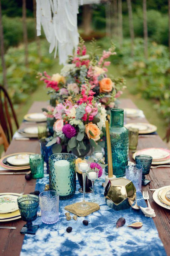 eine boho tablescape mit indigo gefärbt Tischläufer, Smaragd und indigo-Brille und Fett florals