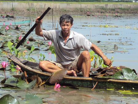 Ông Huỳnh Chấn Kim bên mô hình nuôi tép rêu.