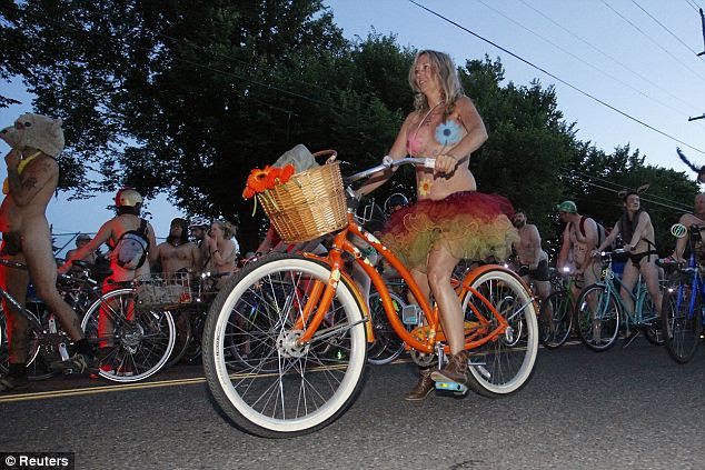 Cruising: Thousands of cyclists, most of them fully of partially nude, poured into the streets of Portland, Oregon on Saturday night for World Naked Bike Ride