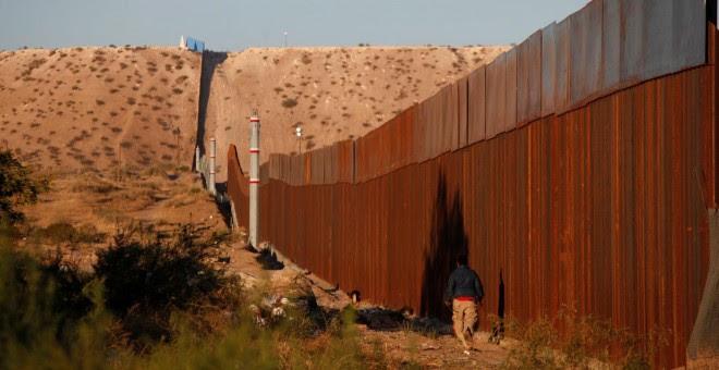 Un hombre pasa por una sección del muro que separa EEUU de México, cerca de Ciudad Juarez. - REUTERS