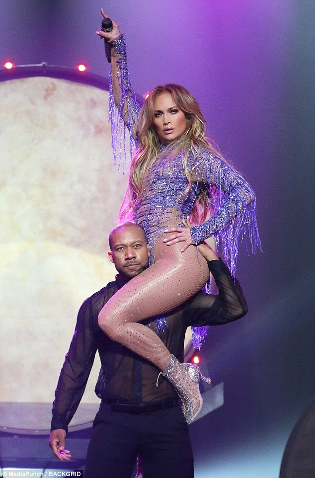 Helping hand: She best showcased her enviable assets thanks to the man carrying her around the stage during her live performance