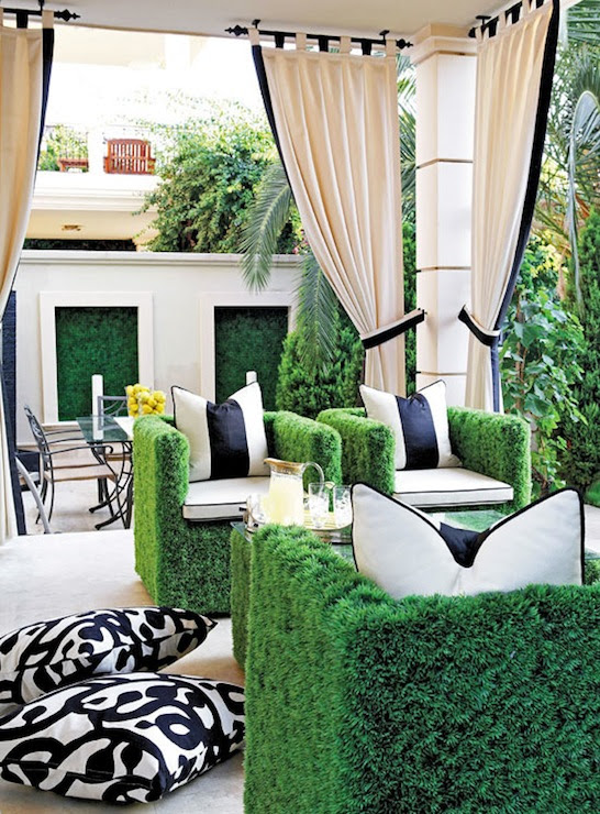 Chic patio with faux grass chairs found in paris black and white outdoor pillows, black and white outdoor curtains