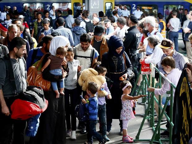 Refugiados caminham por estação após desembarcarem em Munique neste domingo (13) (Foto: Michaela Rehle/Reuters)
