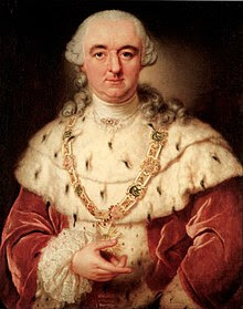 A white whigged man with a crimson coat and an ermine mantle holds a medallion in his hand. The medallion has a bright green stone in the center, and is encircled by a star-burst, and it hangs from a jewel-studded chain around his neck.