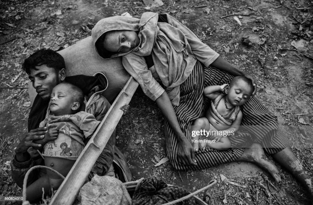 COX'S BAZAR, BANGLADESH - OCTOBER 02: Rohingya refugees Minara Hassan and her husband Ekramul lay exhausted on the ground on Bangladesh side of the Naf River after fleeing their home in Maungdaw, Myanmar, on October 2, 2017 in Cox's Bazar, Bangladesh. More than half a million Rohingya refugees have flooded into Bangladesh to flee an offensive by Myanmar's military that the United Nations has called 'a textbook example of ethnic cleansing'. The refugee population is expected to swell further, with thousands more Rohingya Muslims said to be making the perilous journey on foot toward the border, or paying smugglers to take them across by water in wooden boats. Hundreds are known to have died trying to escape, and survivors arrive with horrifying accounts of villages burned, women raped, and scores killed in the 'clearance operations' by Myanmar's army and Buddhist mobs that were sparked by militant attacks on security posts in Rakhine state on August 25, 2017. What the Rohingya refugees flee to is a different kind of suffering in sprawling makeshift camps rife with fears of malnutrition, cholera, and other diseases. Aid organizations are struggling to keep pace with the scale of need and the staggering number of them - an estimated 60 percent - who are children arriving alone. Bangladesh, whose acceptance of the refugees has been praised by humanitarian officials for saving lives, has urged the creation of an internationally-recognized 'safe zone' where refugees can return, though Rohingya Muslims have long been persecuted in predominantly Buddhist Myanmar. World leaders are still debating how to confront the country and its de facto leader, Aung San Suu Kyi, a Nobel Peace Prize laureate who championed democracy, but now appears unable or unwilling to stop the army's brutal crackdown.