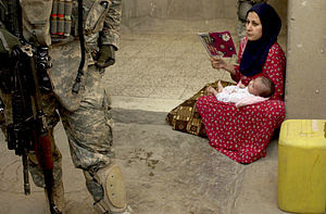 An Iraqi woman looks on as U.S. Army Soldiers ...