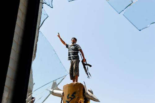 Jeune combattant rebelle posant sur le monument célébrant l'échec des bombardements américains de 1986.