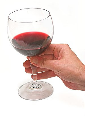 A hand holding a glass of wine.