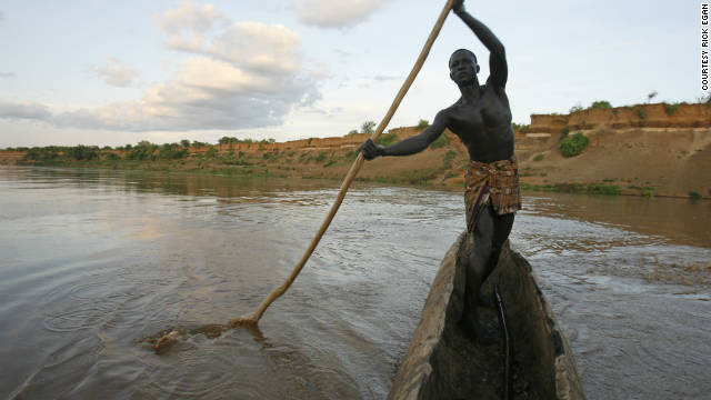"""Kara tribe member Bona Shapo navigates his way across the Omo River in a boat made out of a hollowed log. Shapo says the river is a place where some of the mingi killings take place. """"Sometimes they take the babies out in a boat. Other times, they just take them to the edge of the water and throw them in."""""""