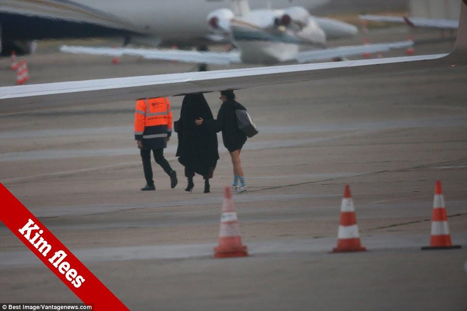 Kim Kardashian foi acompanhada por sua assistente e guarda-costas pessoal como ela correu para um plano de espera na segunda-feira de manhã depois de ser assaltados à mão armada