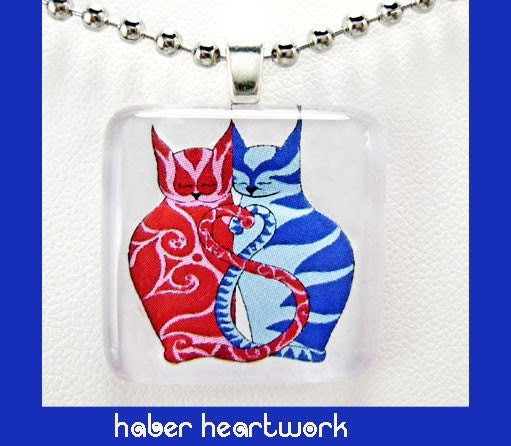 red and blue cats in a glass pendant necklace