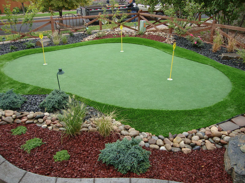 mini size putting green with yellow signs surrounded by green grass carpet and some plant ornaments and river rocks feature wood fence system for golf yard