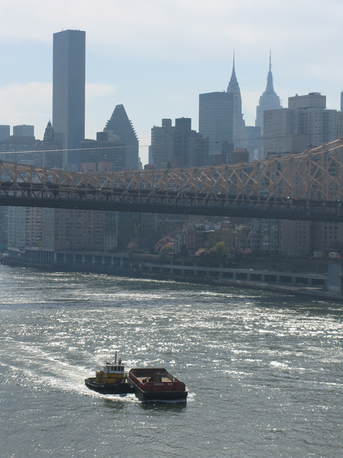 tug boat pushing a barge on the East River, NYC