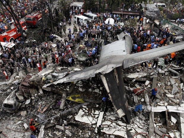 Forças de segurança e equipes de resgate examinam os destroços de um avião militar indonésio C-130 Hercules após queda em uma área residencial na cidade de Medan, na Indonésia. Pelo menos 38 pessoas morreram no acidente (Foto:  Roni Bintang/Reuters)