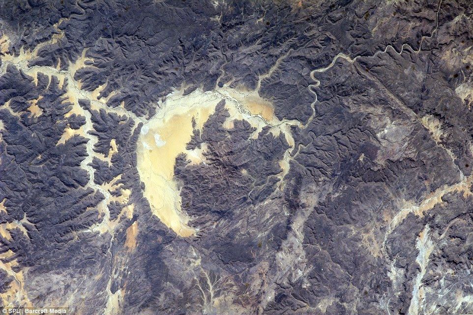 Origins of life? The Gweni-Fada impact crater, seen here in April, is estimated to be around 345 million-years-old. This year, a number of studies have taken a look at how impacts on early Earth could have delivered chemicals essential for life