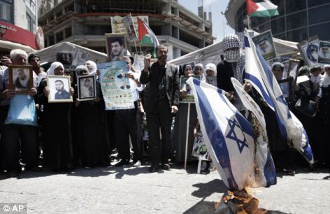 Anger: Palestinians burn Israeli flags during the Ramallah rally for the hunger striker