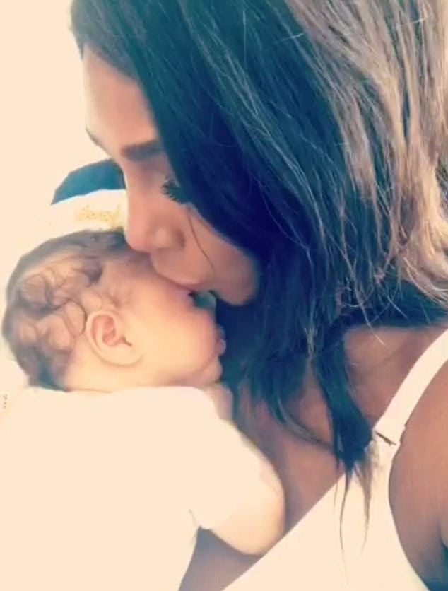 New mom: The tennis star tenderly kissed her six-week-old tot as she rested on her chest