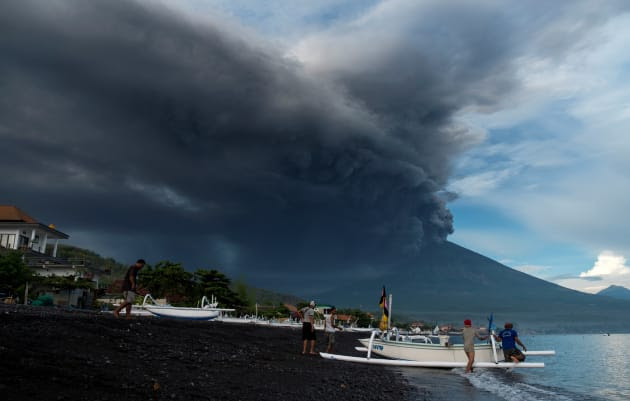 Indonesia's Mount Agung volcano erupts as fishermen pull a boat onto the beach in Amed.