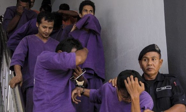 Malaysian Police escort men suspected of gang-raping a 15-year-old girl in Kelantan, Malaysia on May 20