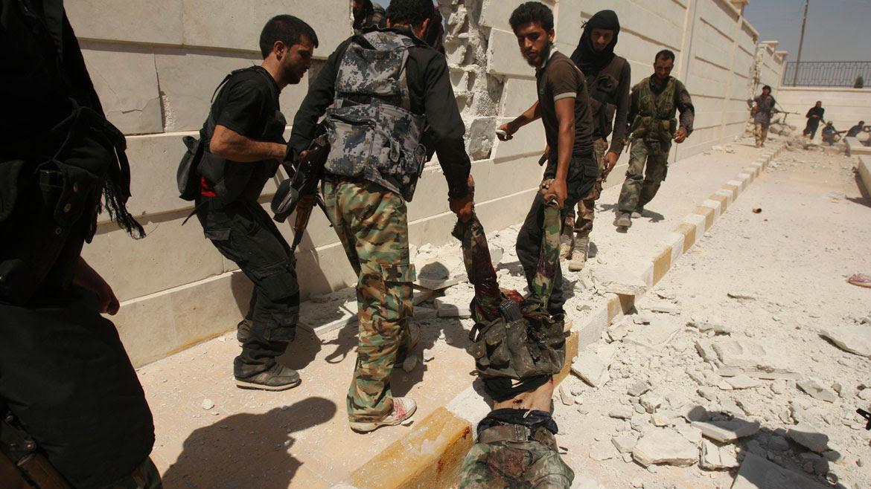 Un grupo de rebeldes arrastra a un soldado regular que acababan de matar