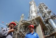 Iraqi workers stand outside the second refinery for crude oil in the Al-Dora refinery complex during its official opening ceremony in Baghdad in September 2010. Iraq's oil exports reached their highest level in more than three decades last month as the country's output has continued to increase, oil ministy officials said.